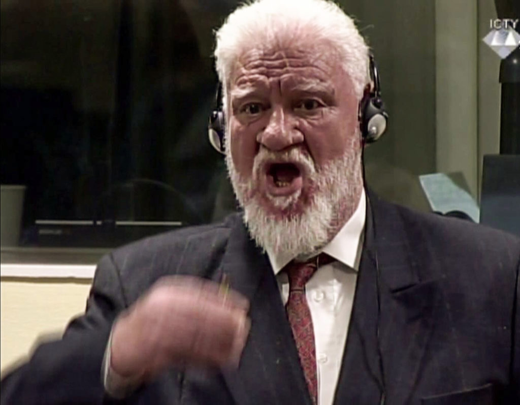This videograb taken from live footage of the International Criminal Court, shows former Croatian General Slobodan Praljak starting to swallow what is believed to be poison, during his judgement at the UN war crimes court to protest the upholding of a 20-year jail term.