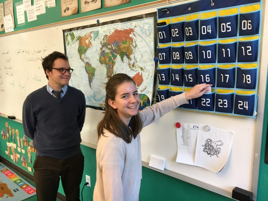 Washington Latin PCS 9th grader Lydia Moore tucks her phone into its designated pocket for Arabic class, as teacher Joe Hamd looks on.