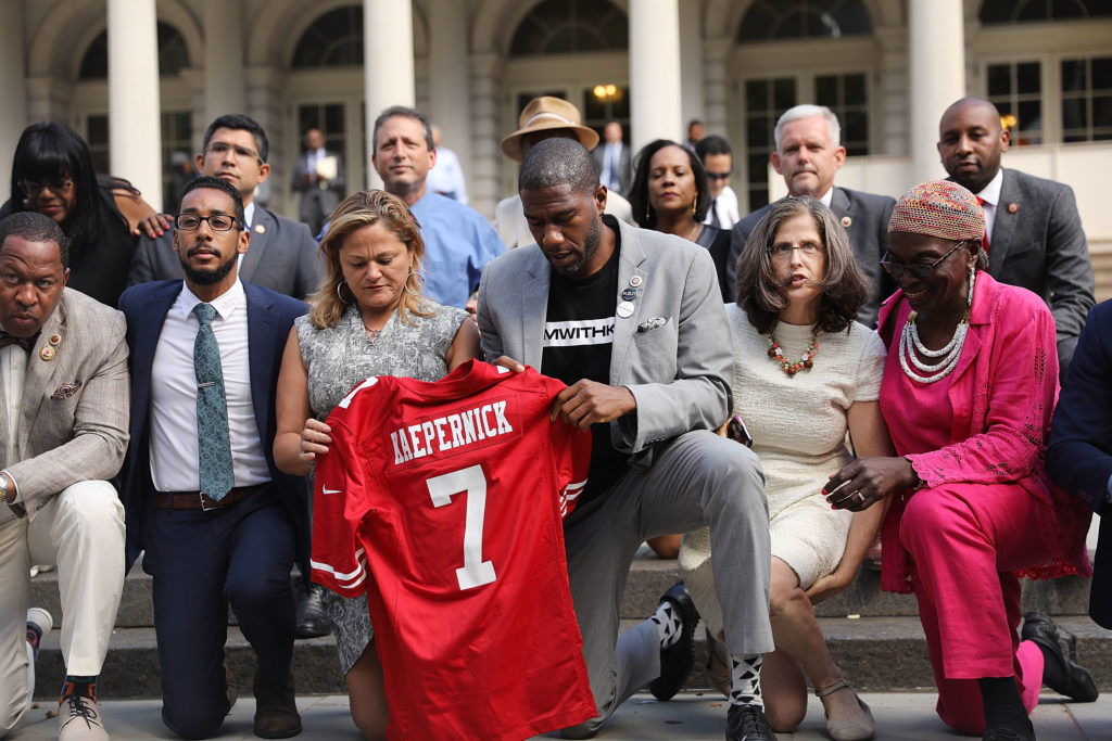 City Council Members 'take a knee' on the steps of New York City Hall in reaction to President Donald Trump's condemnation of NFL players who do the same on September 27, 2017, in New York City. The Council members spoke of having solidarity with athletes and coaches around the country who have also kneeled in protest of racial injustice, especially in policing. Council member Jumaane Williams held a football jersey with quarterback Colin Kaepernick's name on it.