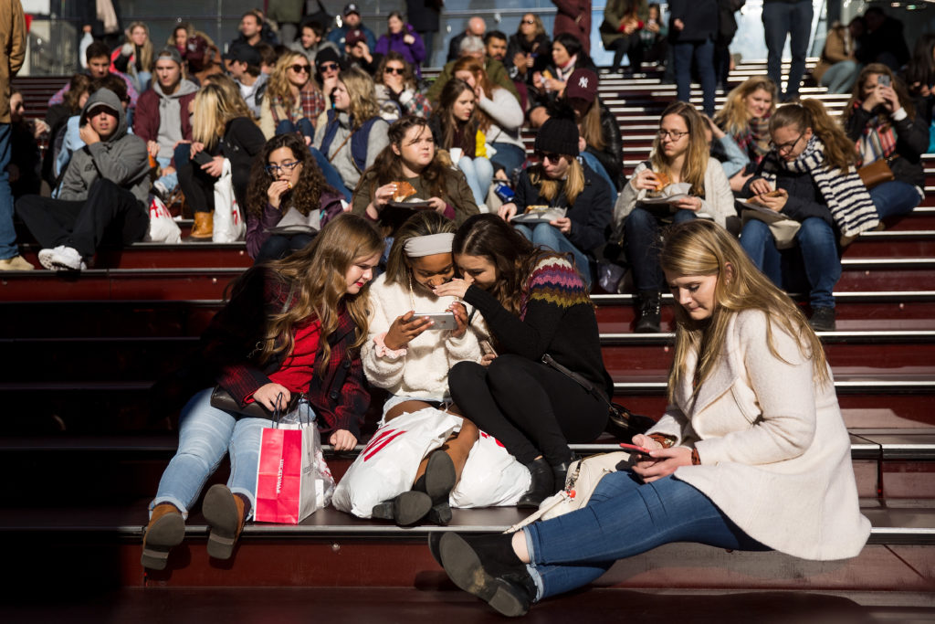 A group of teens look at a photograph they took on a smartphone in Times Square, December 1, 2017, in New York City.
