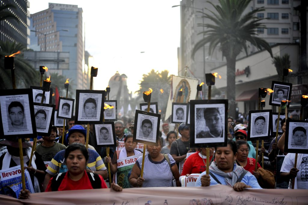 The parents of 43 missing students from Ayotzinapa teachers school hold their portraits and torches during a march 18 months after their disappearance in Mexico City on April 26, 2016.