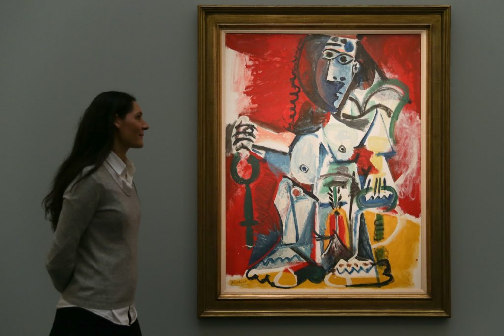 "An employee poses with an artwork by Spanish artist Pablo Picasso, entitled ""Femme nue assise, 1965"", with an estimated price of 9.5-12.5 million GBP (11-15 million EUR; 12-15.5 million USD), during a photocall ahead of the Impressionist & Modern, Surrealist and Contemporary Art sale at Sotheby's in London, on February 22, 2017."