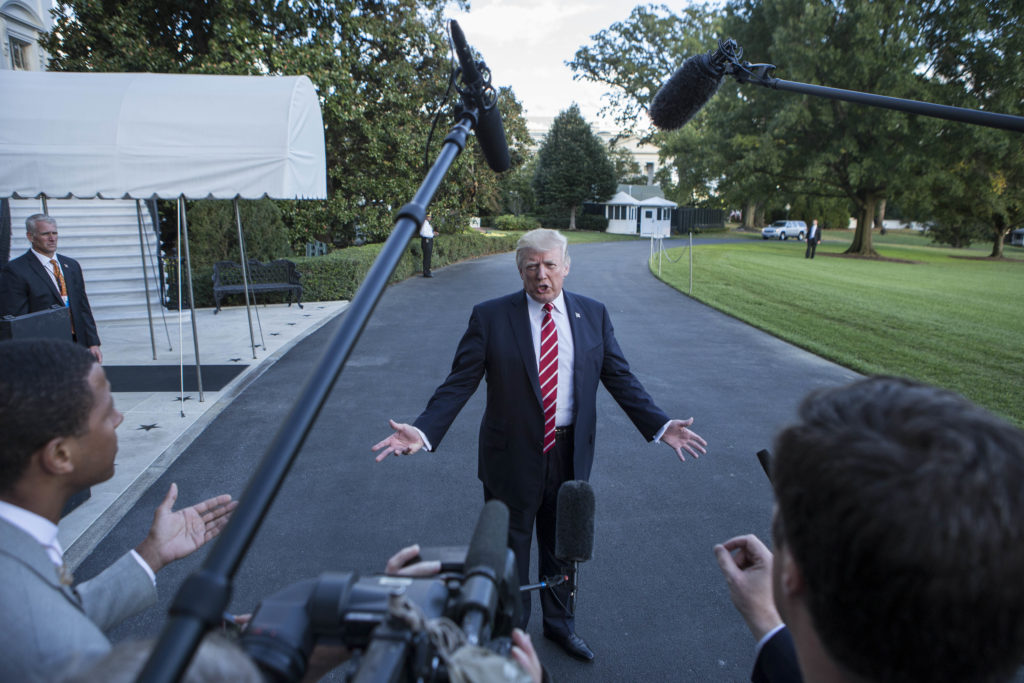 """US President Donald Trump speaks with reporters outside the White House prior to his departure aboard Marine One on October 7, 2017.  During the exchange, President Trump called NBC News, """"Fake News"""" after the news agency reported tension between Trump and US Secretary of State Rex Rex Tillerson. The President will travel to Greensboro, North Carolina this evening to participate in a roundtable discussion with Republican National Committee members."""