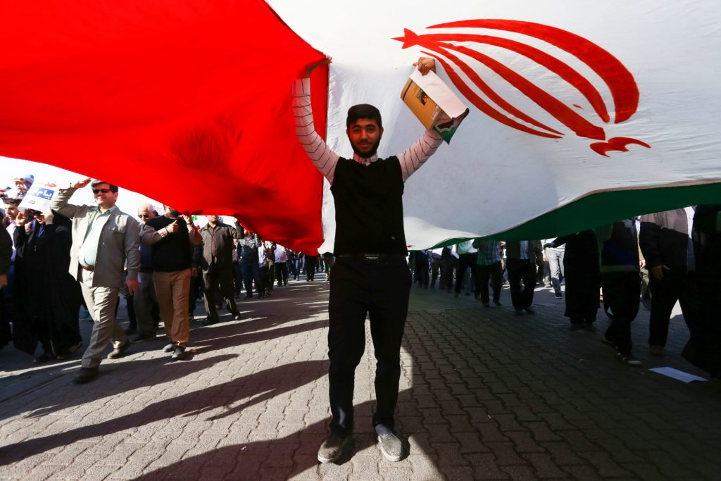 A pro-government demonstrator stands under an Iranian flag during a march in Iran's southwestern city of Ahvaz on January 3, 2018, as tens of thousands gathered across Iran in a massive show of strength for the Islamic rulers after days of deadly unrest.