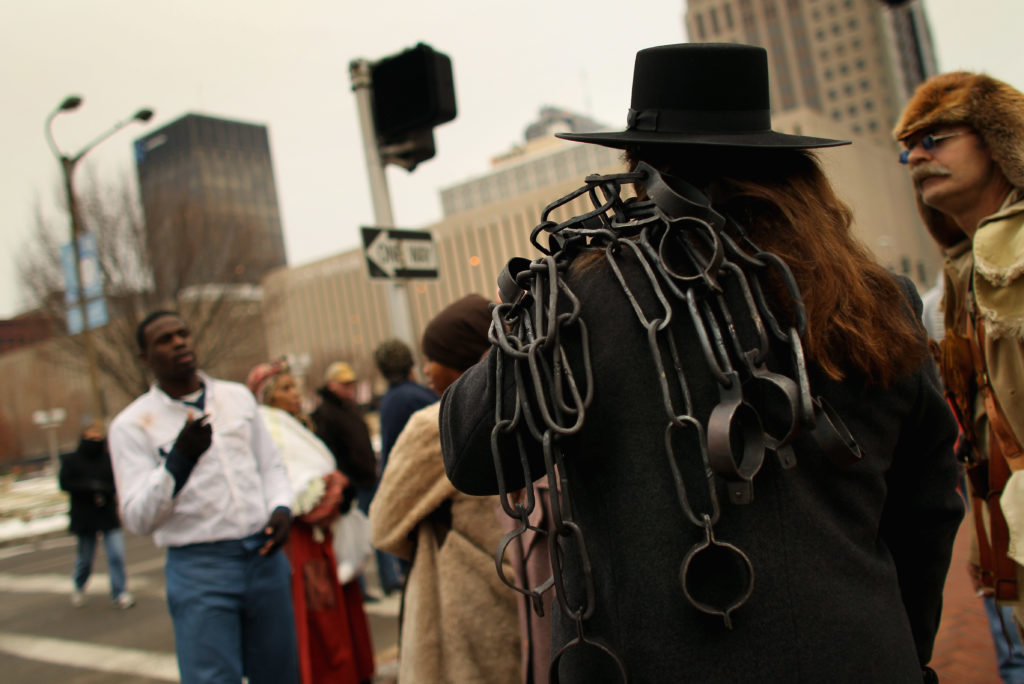 A person portraying a blacksmith carries shackles ahead of a re-enactment of a mid-19th century slave auction in downtown St. Louis, Missouri.