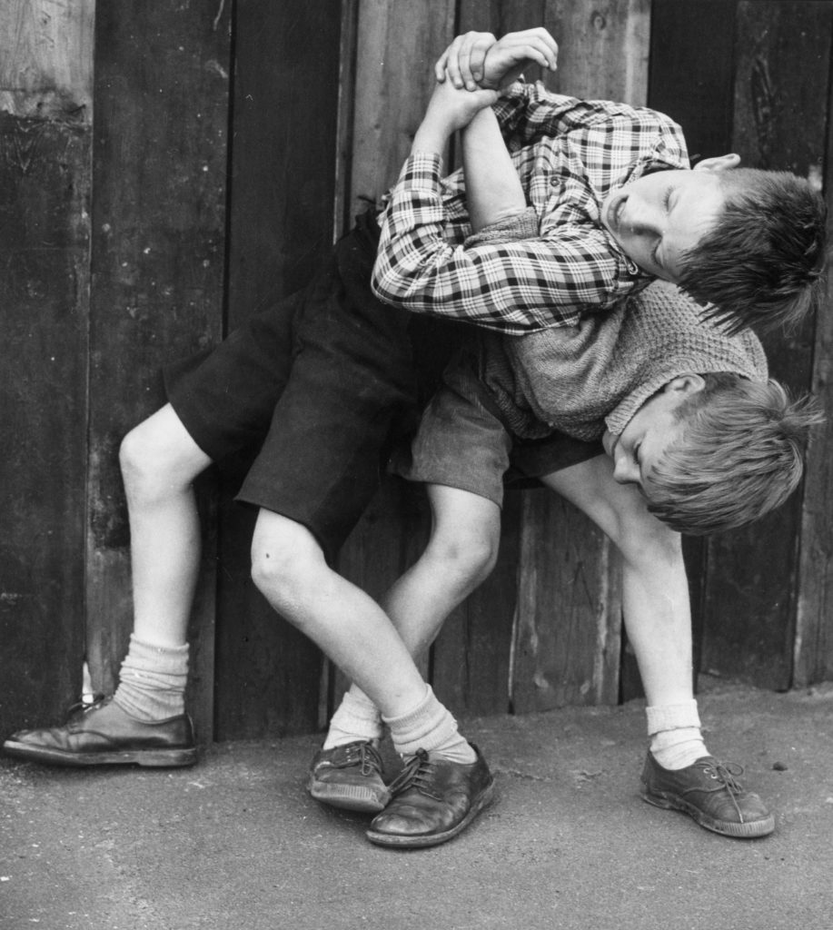 Two young boys wrestling in fun; one has the other in an arm-lock circa 1955.