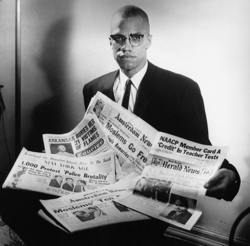 Portrait of human rights activist Malcolm X reading stories about himself in a pile of newspapers, circa 1963.
