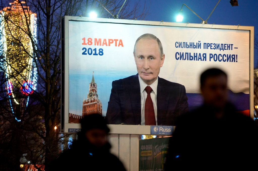 """People pass by a billboard with an image of Russia's President Vladimir Putin and lettering """"Strong president - Strong Russia"""" in Saint Petersburg. Russia's presidential election is scheduled for March 18, 2018, though in the U.S., politicians are watching how Russia may attempt to interfere with the U.S. elections in 2018."""