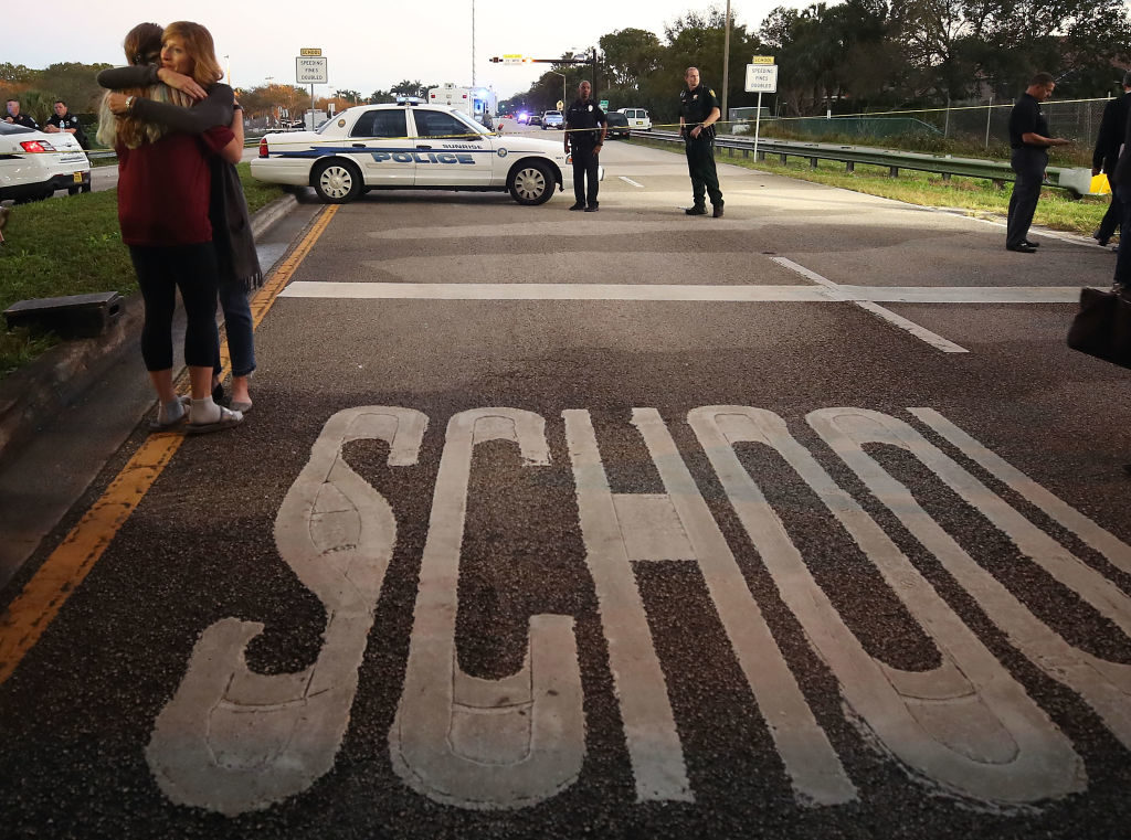Kristi Gilroy (R), hugs a young woman at a police check point near the Marjory Stoneman Douglas High School where 17 people were killed by a gunman on February 15, 2018 in Parkland, Florida.