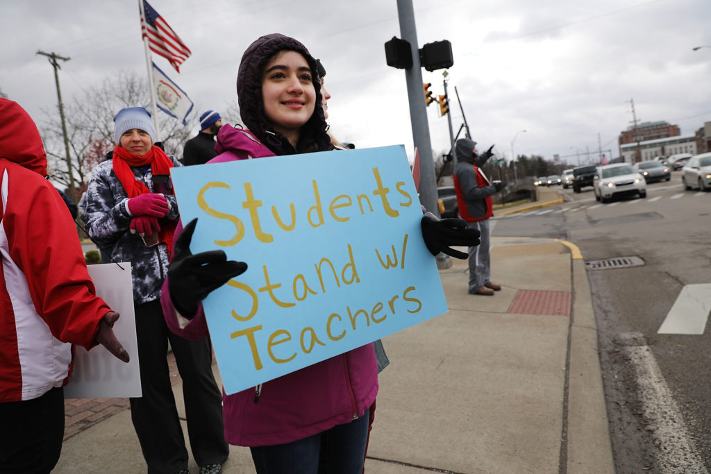 West Virginia teachers, students and supporters hold signs on a Morgantown street as they continue their strike on March 2, 2018 in Morgantown, West Virginia. Despite a tentative deal reached Tuesday with the state's governor, teachers across West Virginia continued to strike on Friday as the Republican-controlled state legislature debated the governor's deal.